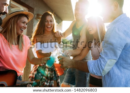 Young friends having fun at a rooftop party, playing the guitar, singing, dancing and drinking #1482096803