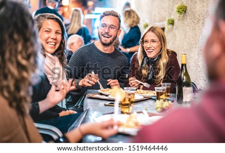 Young friends having fun drinking white wine at street food festival - Happy people eating local plates at open air restaurant together - Travel and dinning lifestyle concept on bulb light neon filter
