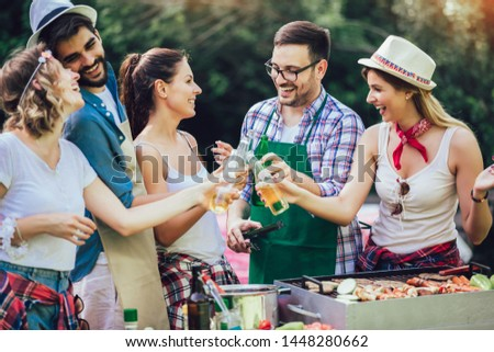 Young friends having fun grilling meat enjoying barbecue party. #1448280662