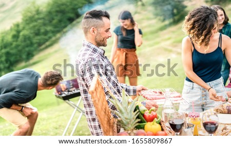 Young friends having fun on outdoors picnic preparing food at barbecue grill party - Happy people cooking and eating at countryside open air restaurant - Youth friendship concept on bright warm filter Stockfoto ©