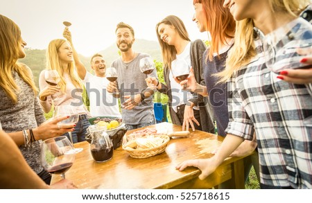 Young friends having fun outdoor drinking red wine - Happy people enjoying harvest time at farmhouse vineyard winery - Youth friendship concept with focus on guy toasting in middle frame - Warm filter