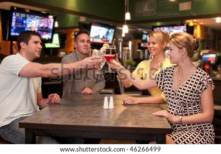 Young friends  in a modern bar and lounge toasting.
