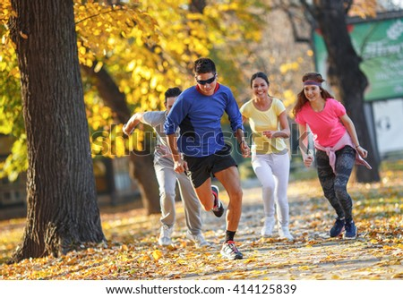 Young friends jogging at the park.Autumn season. #414125839