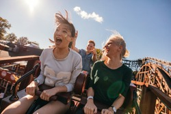 Young friends on thrilling roller coaster ride. Young women and men having fun at amusement park.