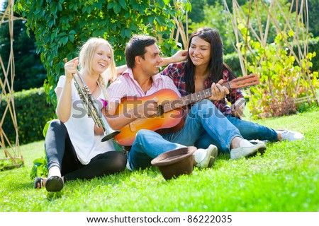 Young friends play the guitar and trumpet in the park #86222035