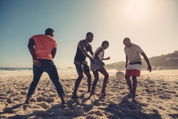 Young friends playing football on the sandy beach. African people enjoying a game of soccer on summer day.