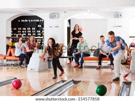 Young friends playing in bowling alley with people in background
