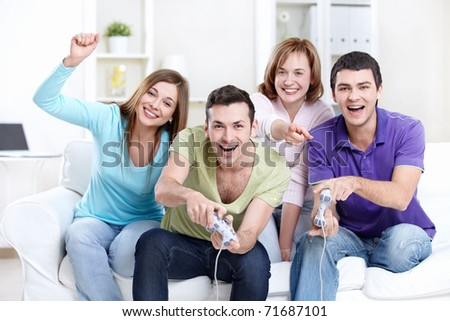 Young friends playing video games at home