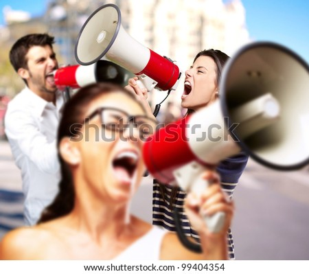young friends screaming with megaphone against a building - stock photo