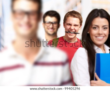 young friends smiling and one biting a pen
