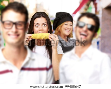 young friends smiling and one middle aged woman cook at street