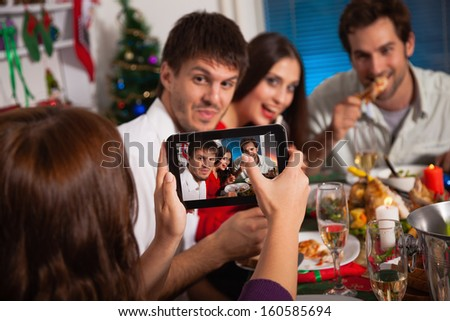 Young friends taking picture with digital tablet on Christmas eve.