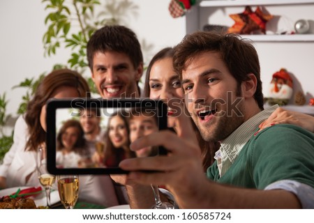 Young friends taking self portrait with digital tablet on Christmas eve.
