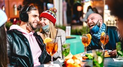 Young friends talking at winter cocktail bar outdoors wearing open face mask - New normal lifestyle concept with millennial people having fun together - High iso image with focus on girl with hat