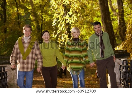 Young friends walking in autumn park, holding hands, smiling.?