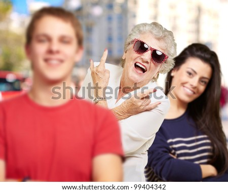 young friends with grandmother having fun at street
