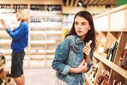 Young frightened woman in denim jacket trying steal bottle of wine in modern supermarket