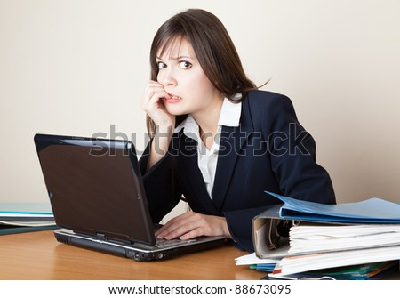 Young frightened woman is looking at the laptop screen