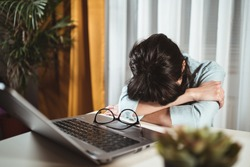 Young frustrated exhausted woman laid her head down on the home office desk. Fatigue female worker doing overtime project during pandemic. Achievement business career and overtime work concept
