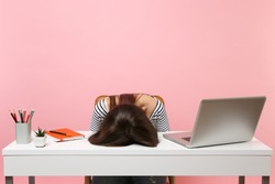 Young frustrated exhausted woman laid her head down on the table sit work at white desk with contemporary pc laptop isolated on pastel pink background. Achievement business career concept. Copy space
