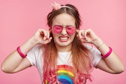 Young frustrated stylish female likes pink colour, blocks ears as hears loud music on party, has headache, clenches teeth, wants silence, isolated over pink background. Cute lovely girl plugs ears