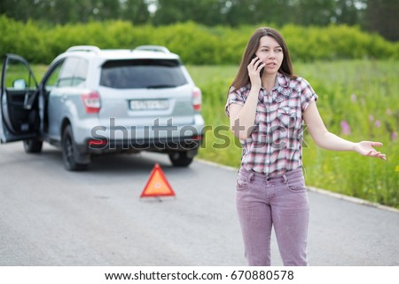 Young frustrated woman with flat tire on broken car phoning for assistance #670880578