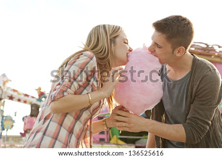 Young fun couple biting into a cotton candy floss sweet at the same time while visiting an amusement park during a sunny day.