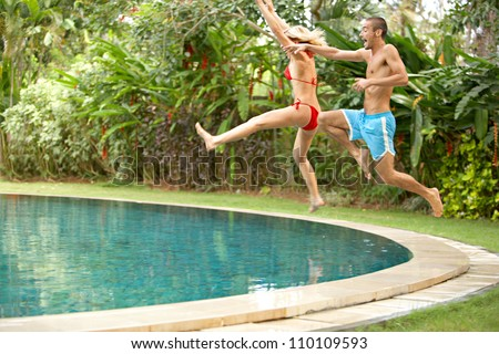 Young fun couple jumping into a tropical swimming pool while on vacations in a tropical destination.