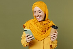 Young fun satisfied happy arabian asian muslim woman in abaya hijab yellow clothes hold paper cup of coffee use mobile cell phone isolated on olive green background People uae islam religious concept