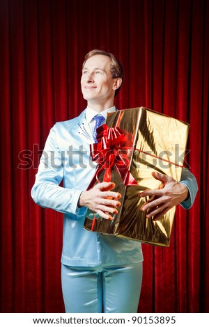 Young, funny, attractive and happy  man taking a gift dressed in blue suite on a red background