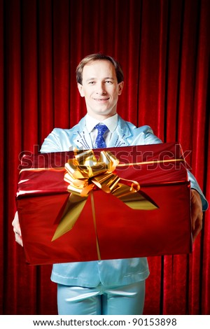 Young funny,attractive man presenting a gift dressed in blue suite on a red background