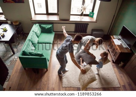 Young funny family playing pillows fight with toddler son and daughter in living room at home, happy, excited mother and father with children, family spending great time together, top above view