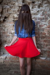 young funny girl, pale, with long brown hair all over she face, and glasses over the hair, the blue shirt from jeans and red skirt that was spread, standing in front of a brick wall.