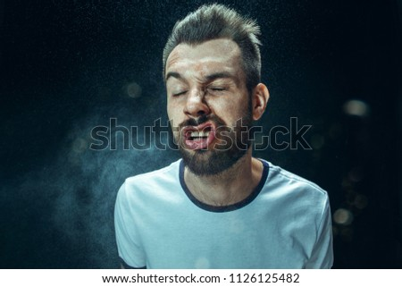 Young funny handsome man with beard and mustache sneezing with spray and small drops, studio portrait on black background. Comic, caricature, humor. illness, infection, ache. Health concept