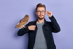 young funny man with owl in his arm pretending Harry Potter. isolated blue background, cosplay, lifestyle, free time, spare time