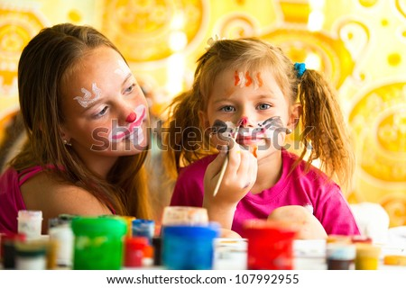 Young funny sisters playing with painting