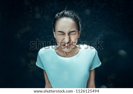 Young funny woman sneezing with spray and small drops, studio portrait on black background. Comic, caricature, humor. illness, infection, ache. Health concept