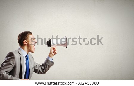 Young furious man screaming agressively in megaphone