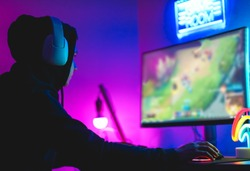 Young gamer playing at strategy online game - Male guy having fun gaming and streaming online - New technology game trends and entertainment concept - Soft focus on his hand
