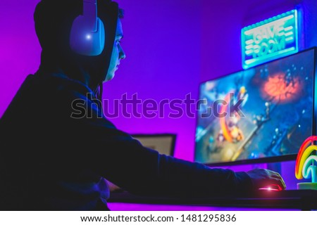 Young gamer playing at strategy online game - Male guy having fun gaming and streaming online - New technology game trends and entertainment concept - Focus on his hand