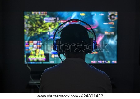Photo of  Young gamer playing video game wearing headphone.