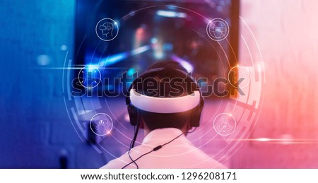 Young gamer wearing VR goggles and headset with icon VR playing and winning driver and shooter online video game on his personal computer in the room lit by neon lights, eSport network online.