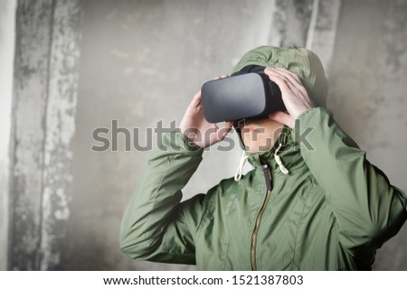 young gamer with virtual reality headset in a green protective jacket with a hood, a serious teenager with vr glasses during the gameplay, modern technology will affect the future