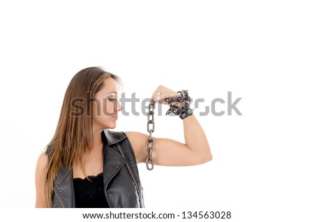 Young gang girl showing her biceps in studio with chains