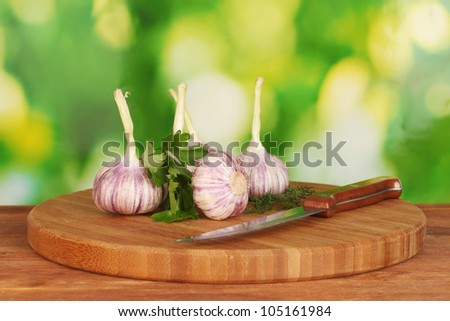 young garlic on cutting board with greenery and knife on wooden table on green background