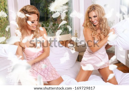 Young gay couple fighting pillows in the bedroom