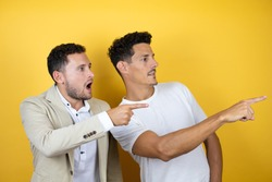 Young gay couple of two men wearing casual clothes over isolated yellow background pointing with finger surprised ahead, open mouth amazed expression, something on the front
