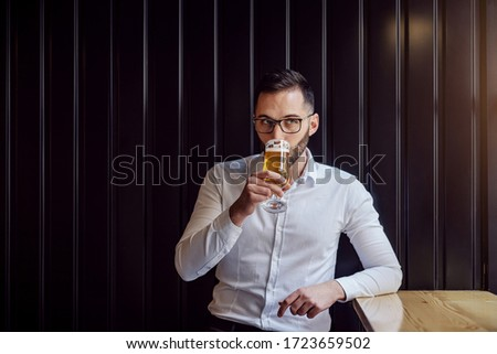 Young geeky businessman leaning on the table next to window drinking beer.