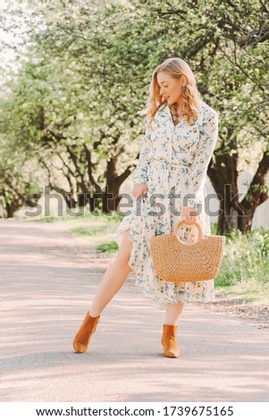 Young gentle carefree woman in white retro floral dress posing with stylish straw dress in countryside park. Beautiful happy blonde hippie girl walk and relax on green garden. Tender lady enjoy nature