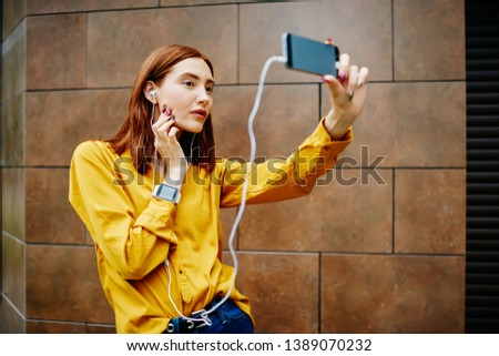 Young ginger hipster girl posing for selfie holding modern cellular and listening playlist in earphones outdoors, female blogger shooting video for followers via smartphone camera and 4G internet
